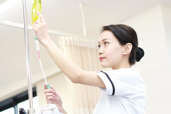点滴器具の調節をする女性